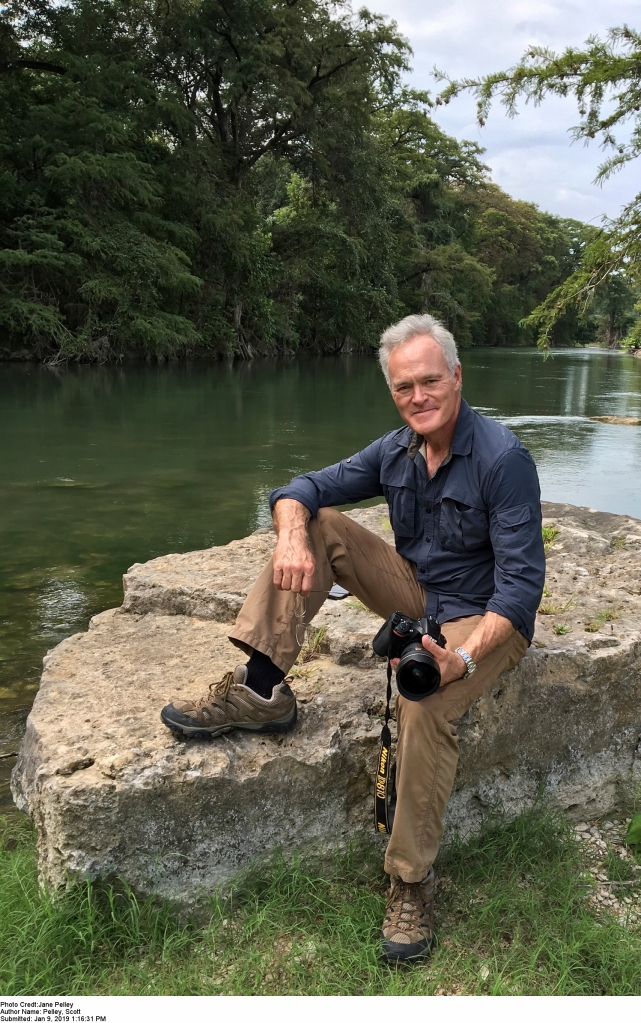 Scott Pelley sitting on a rock by a river holding a camera